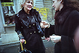 Two women chatting in passing at Preradovicva street on cloudy Saturday.