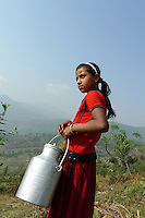 A young girls struggles to haul a metal jug of water along the rim of the Pokhara Valley in Nepal. Pokhara is the starting point for many of Nepal's most popular trekking and rafting destinations, and home to over 350 thousand people.