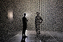 London, UK. 03.10.2012. Random International's experimental, interactive artwork RAIN ROOM opens to the public in The Curve art gallery space at The Barbican Centre. Picture shows: One of the artists, Florian Ortkrass, with a friend, in the Rain Room. Photo credit: Jane Hobson.