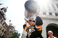 Evgeni Malkin #71 of the Pittsburgh Penguins hoists the Stanley Cup for the crowd during the victory parade in downtown Pittsburgh, Pennsylvania on June 15, 2016. (Photo by Jared Wickerham / DKPS)