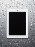 White Apple iPad 2 tablet computer with blank screen on wet gray steel background