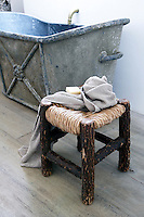 A detail of the bathroom highlights the Empire-style zinc bath and rustic 20th century footstool