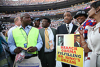 "The Reverend Al Sharpton poses for photographs with a delegate and HER sign saying ""Barack Obama Fulfilling Dr. King's Dream"" on the delegate floor of the Democratic National Convention, Invesco Field, Denver, Colorado, August 28, 2008."