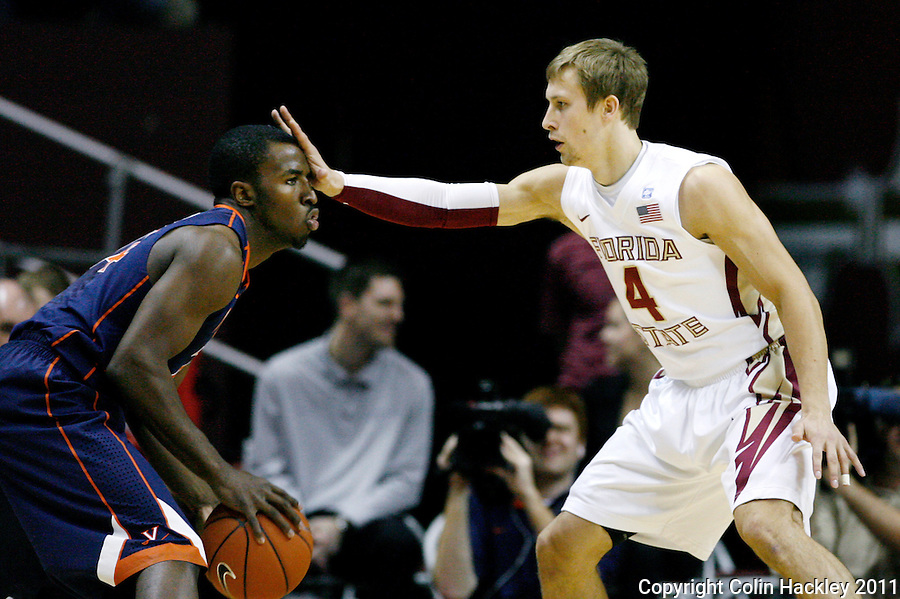 TALLAHASSEE, FL 10-FSU-VA MBB11 CH-Florida State's Deividas Dulkys keeps Virginia's KT Harrell at arm length during first half action Saturday at the Donald L. Tucker Center in Tallahassee...COLIN HACKLEY PHOTO