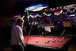 A man working in Columbus from out of town, who wished to be unidentified, plays pool in at the only bar in town. Recently federal authorities arrested the mayor, police chief, and trustees who were allegedly operating an illegal gun running ring.