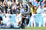 30 November 2013: Duke's Juwan Thompson (23) breaks a tackle by UNC's Mikey Bart (behind). The University of North Carolina Tar Heels played the Duke University Blue Devils at Keenan Memorial Stadium in Chapel Hill, NC in a 2013 NCAA Division I Football game. Duke won the game 27-25.