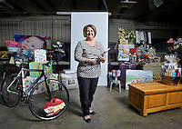 NWA Democrat-Gazette/BEN GOFF -- 03/13/15 Gail Feagans, director of the Miller McNeil Woodruff Foundation's Cupcakes and Cocktails event, poses for a photo in the warehouse where donated items for the event's auction are being processed in Rogers on Friday Mar. 13, 2015.