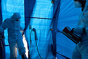 The crew of the Greenpeace ship Rainbow Warrior undertake a 'radiation decontamination' drill, in a purpose built tent at the side of the ship bridge deck, as the ships sails up the eastern coast of Japan on her way to Fukushima, in Japan, Monday 2nd May 2011.