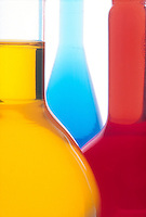 LABGLASS: FLORENCE and VOLUMETRIC FLASKS<br /> Assortment of labglass with chemistry<br /> Orange, blue, red &amp; yellow.