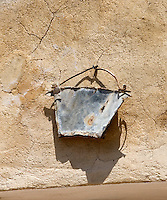A zinc bucket, crushed by one of the builder's trucks, hangs on a wall in the garden as a memento of the restoration works