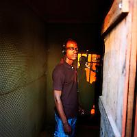 A Kuduru/Kuduro musician recording in a studio built on the top of a shack in the Sambizanga musseque (slum)..