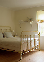 An old-fashioned, cream-painted, wrought-iron bed in a simple bedroom
