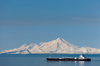Oil tanker travels through Cook Inlet with Mt. Iliamna volcano of the Chigmit mountains of the Aleutian Peninsula mountain range.