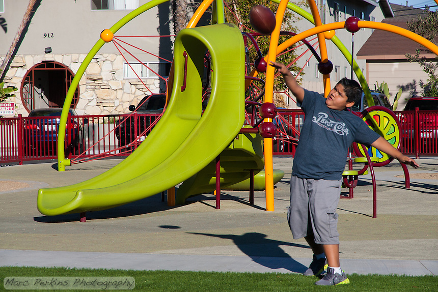 A boy throws a football in front of a play structure at Circle Park, a pocket park located on Park Circle Drive in Anaheim, California.
