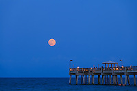 The full moon rises over the public fishing pier at Dania Beach, Florida.