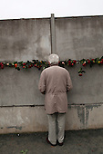 Berlin, Germany.<br /> November 9, 2009<br /> <br /> Young and old a like visit the Wall Museum at a place the wall once stood and place flowers in the wall cracks and light candles on the 20th anniversary of the Fall of the Berlin wall.