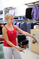 Woman looking and comparing different shoes in shop. Fashion, retail store, shopping.