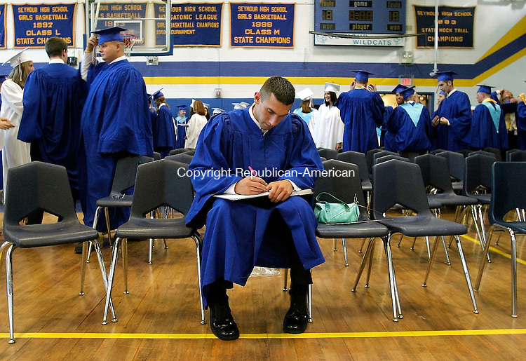 SEYMOUR, CT - 17 JUNE 2005 -061705JS01--Seymour graduating senior Kevan Taggart takes a few moments before the commencement to sign the yearbook of classmate Shannon Naedele Friday at Seymour High School.  --Jim Shannon Photo--Kevan Taggart, Shannon Naedele, Seymour are CQ