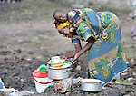 A displaced woman cleans up after cooking a meal for her children. They were left homeless in October 2008 by fighting between forces of rebel Tutsi General Laurent Nkunda and the Congolese government. They took refuge with dozens of other families in a church and adjacent school in the Goma neighborhood of Musawato.  A quarter of a million people have been newly displaced by fighting in the eastern Congo, where some 5.4 million have died since 1998 from war-related violence, hunger and disease.