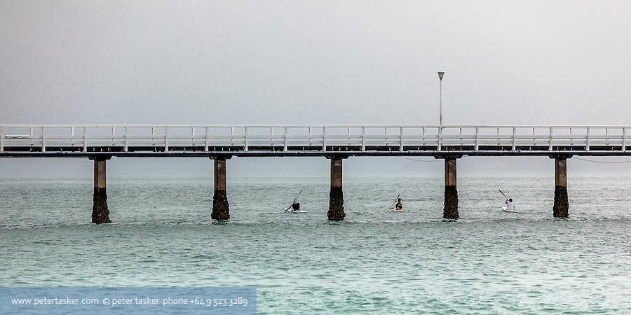 Three kayakers paddling under Orakei Wharf, Okahu Bay, Auckland, New Zealand.