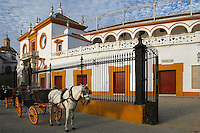 Low angle view of the Plaza de Toros de la Real Maestranza de Caballeria de Sevilla, Seville, Spain, pictured on December 30, 2006, in the afternoon. The Plaza de Toros de la Real Maestranza, 1762-1881, is the oldest bullring in Spain. Its Baroque facade, was built by several architects. A horse and carriage await tourists outside the 16th century iron gates of the Puerta del Principe, by Pedro Roldan, which were originally made for a convent. Picture by Manuel Cohen.