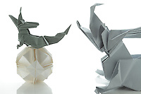 New York, NY, USA - November 4, 2011: Three Origami creations photographed in studio. The wyvern is designed by John Montroll and folded from one piece of paper. The dragon is designed by Kunihiko Kasahara and folded from one square of paper without cuts. The polyhedral  Ishibashi ball is folded from more than one piece of white paper. Esmé Cribb folded all three pieces.