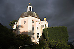"Portmeirion, in North Wales, is a resort, where no one has ever lived. A self-taught Welsh architect named Sir Clough Williams-Ellis built it out of architectural salvage between the 1920s and 1970s, loosely based on his memories of trips to Portofino. Including a pagoda-shaped Chinoiserie gazebo, some Gothic obelisks, eucalyptus groves, a crenellated castle, a Mediterranean bell tower, a Jacobean town hall, and an Art Deco cylindrical watchtower. He kept improving Portmeirion until his death in 1978, age 94. It faces an estuary where at low tide one can walk across the sands and look out to sea. At high tide, the sea is lapping onto the shores. Every building in the village is either a shop, restaurant, hotel or self-catering accomodation. The village is booked out at high season, with numerous wedding receptions at the weekends. Very popular amongst the English and Welsh holidaymakers. Many who return to the same abode season after season. Hundreds of tourists visit every day, walking around the ornamental gardens, cobblestone paths, and shopping, eating ice-creams, or walking along the woodland and coastal paths, amongst a colourful assortment of hydrangea, rhododendrons, tree ferns and redwoods. The resort boasts two high class hotels, a la carte menus, a swimming pool, a lifesize concrete boat, topiary, pools and wishing wells. The creator describes the resort as ""a home for fallen buildings,"" and its ragged skyline and playful narrow passageways which were meant to provide ""more fun for more people."" It does just that.///The Dome Gallery at sunset with storm clouds behind"
