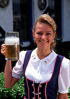 Portrait of a smiling waitress at a Munich Biergarten in traditional German dress holding a stein of beer. Germany.
