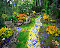 Vashon Island, WA<br /> Whimsical garden of tile artist Clare Dohna featuring snake pathway of moasic tiles and round stones