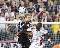 San Jose Earthquakes defender Brad Ring (5) and New England Revolution substitute forward Dimitry Imbongo (92) battle for head ball.  In a Major League Soccer (MLS) match, the New England Revolution (white) defeated San Jose Earthquakes (black), 2-0, at Gillette Stadium on July 6, 2013.