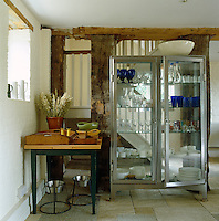 A refurbished medical cabinet displays an assortment of glass and china in a corner of the kitchen area