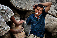 "A young Honduran immigrant, having his arm amputated by a train during his previous attempt to get illegally to the United States, smokes marijuana on the bank of Suchiate river on the Guatemala-Mexico border, on 23 May 2011. Between 2010 and 2015, the US and Mexico have apprehended almost 1 million illegal immigrants from El Salvador, Honduras, and Guatemala. While the economic reasons remain the most frequent motivation for people from Central America to illegally immigrate to the US, thousands of Salvadorans, Guatemalans, and Hondurans, many of them minors, seek asylum in the US due to the thriving crime and gang-related violence in their region (known as the Northern Triangle). Taking an exhausting and risky journey, riding thousands of miles atop the cargo trains, facing a physical danger and extortion from the organized crime groups that control migrant routes, the ""undocumented"" still flee to the US, looking for their American dream."