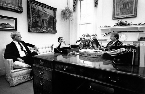 United States President Jimmy Carter, right, chief speechwriter Jim Fallows, center, and US Secretary of Energy James R. Schlesinger, left, apply last-minute touches to the scheduled energy address to the nation on live television in the evening at the White House in Washington, DC on April 18, 1977.  In his remarks, the President will equate the energy crisis as the &quot;moral equivalent of war.&quot;<br /> Credit: White House via CNP