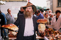 October 1992, Alba, Italy --- Grocer Holding Large Porcini Mushrooms --- Image by &copy; Owen Franken - Photograph by Owen Franken