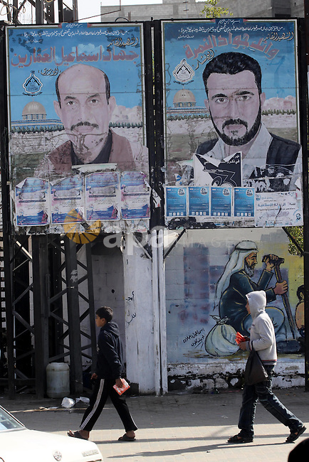 Palestinian children walk past posters depicting the leaders of Al-Aqsa Martyrs Brigades, Jihad Al-Ammarin and Wail Al-Nimra, in Gaza City on Jan. 26,2011. Palestinian factions accused the Palestinian Authority in the West Bank, being involved in assassination of Jihad Ammarin and other militants in al-Aqsa Martyrs Brigades, as well Hassan Madhoun according to the published Al-Jazeera's secret documents. Photo by Mohammed Asad