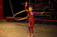 "Circus young girl performs with hula hoops. Bentley Bros. circus, one of the few remaining ""mud show"" circus performing under a canvas big top."