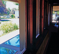 F.L. Wright: Darwin D. Martin House. Detail: looking out south facing windows. Sunlight in winter refracts off uneven surface of skylight beneath as off water.   Photo '88.