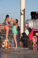 Two girls stand in the splash pad of Stanton Central Park in bathing suits, looking happy has water flies around them.  A boy hides in the shadow to their right.  One of the girls is standing on an animal.