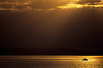 Storm clouds off Alki Point with silhouetted boat and men fishing sunset Seattle Washington State USA.