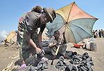 A woman and her children, left homeless by war, sell charcoal in a camp in rebel-held territory in the eastern Congo. Families displaced by fighting between rebel Tutsi General Laurent Nkunda and the Congolese military took refuge in this camp they established in the shadow of a United Nations base in the village of Kiwanja. According to aid workers and human rights groups, rebel soldiers executed some 150 people here in a 24-hour period in early November. The killings took place half a mile from the UN base, yet the 120 UN peacekeepers, part of the largest UN peacekeeping contingent in the world, did not take any action to stop the violence. ..