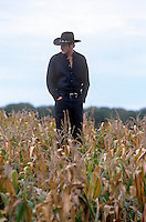 man in black clothing and a cowboy hat standing in a cornfield