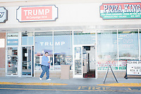 Trump supporter John Collins, of Warwick, Rhode Island, carries signs out of the Rhode Island state campaign headquarters for Republican presidential candidate Donald Trump at the Airport Plaza strip mall in Warwick, Rhode Island, USA, on Sun., Apr. 24, 2016. The campaigns of Trump, Cruz, and Kasich, have all set up offices in the strip mall.