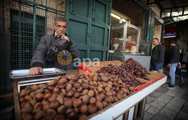 A Palestinian vendor sells chestnut and dates at a street market in Jerusalem's Old City on February 12, 2014. Minister of Holy Places for the PA Mahmoud al-Habbash told Israel's Channel 10 network that the PA wants control of all the areas in Jerusalem that were won by Israel during the 1967 Six-Day War, including the Western Wall. Photo by Saeed Qaq