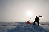 Pilot positioning a sound beacon on an ice floe that sends signals to the icebreaker indicating the location and speed of ice floes so the ship can best move though the ice pack. As the ship and the ice pack drifts, pilots continually have to go out and pick up ice buoy stations drifting out of the range of the ship and reposition them closer.
