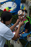 Native American , Chaske Hill Sicangu Lakota and Seneca , mother dressing and preparing her 3 year old son for pow wow dance contest at the Thunderbird powwow in Queens, NY .
