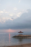 Sanur Beach, Bali, Indonesia; small, temple shaped structures along the beach boardwalk contain benches for quiet reflection while looking out over the water at sunrise