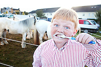 3/10/2010.  12 year old traveller Martin Connors from Wexford cleans his teeth outside his caravan at the Ballinasloe Horse Fair, Ballinasloe, County Galway, Ireland. Picture James Horan