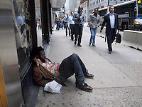 USA. New York City. A black afro-american homeless man sleeps on the pavement on Madison Avenue. Crowds walking in Midtown Manhattan. Lunch hour. MTA public city bus. 21.10.2011 &copy; 2011 Didier Ruef