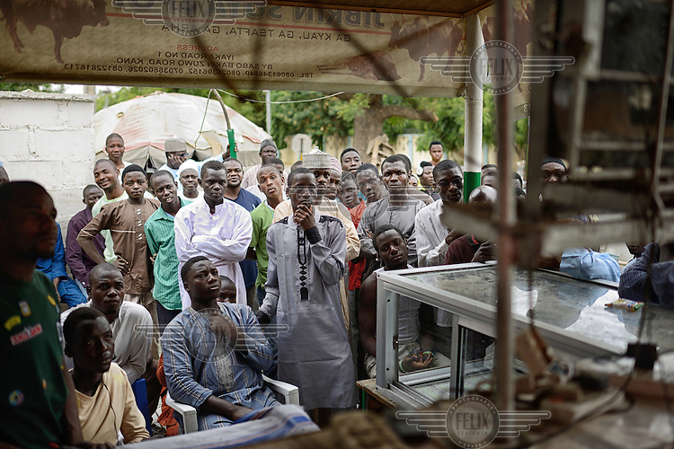 A group of men, gathered around a television broadcasting election news in a small market stall, watch as the latest results from the 2015 Presidential elections are revealed to the nation. Initial results indicated a tight race but as the counting of votes progressed it soon became clear that Muhammadu Buhari, leader of the APC (All Progressives Congress Party), had prevailed.