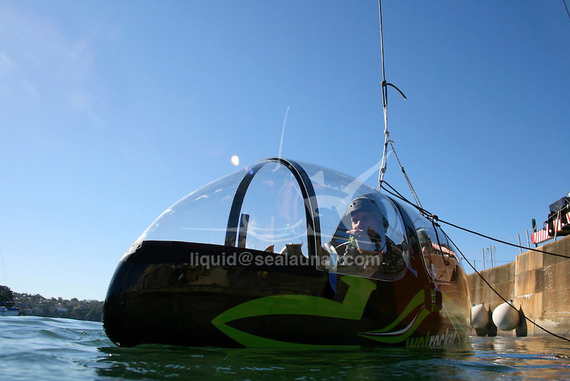 Australia's attempt to reclaim the 500m world speed sailing record..Pilot Sean Langman and co-pilot Martin Thompson practicing an emergency evacuation from the upside down pod of Wot Rocket in the waters off Woolwich Dock.The Wot Rocket is half sailboat/sail plane; a nine meter long canoe style hull with two tiny foils, each about a sixth of the size of a Moth foil and a nine meter rigid sail, then a traverse beam out of an aerodynamic twin pod crew compartment. It is built entirely from carbon fiber  and weighs approximately 400 kilos.The difference between this sailboat/sail plane and any that have come before it is that it will be attempting to break through the water speed barrier using a technology as yet untried on any sailing craft - supercavitation - to reduce the drag which is around 1,000 times greater in the water than in air..Supercavitation will in effect mean Wot Rocket flies in a gas bubble created by the outward deflection of water by a specially shaped nose cone and the expansion of gases from its fin and foil design. By keeping water from contacting the surface of the body of Wot Rocket, this will significantly reduce drag and allow extremely high speeds. .The concept behind the Wot Rocket approach is to induce supercavitation at lower speeds where control can still be maintained and from there push through to the top speeds.Supercavitation means Wot Rocket should only require a fraction of the 45-50 knot winds that Albeau needed to go 0.39 knots better than the previous record. A moderate 18-20 knots should do the trick believes Langman.